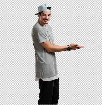 Hombre joven del rapero que sostiene algo con las manos, mostrando un producto, sonriendo y alegre