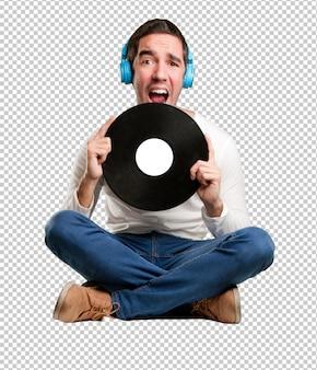 Hombre joven sentado con unos auriculares y gritando