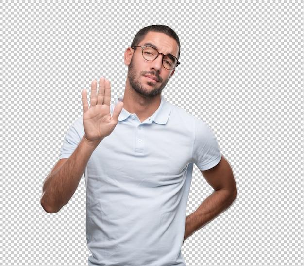Hombre joven serio haciendo un gesto de parada
