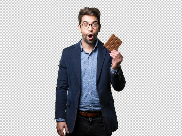 Hombre joven sorprendido que sostiene una barra de chocolate