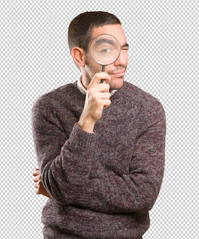 Hombre joven sorprendido que usa una lupa