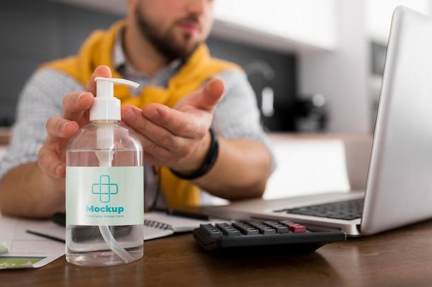 Hombre con laptop usando maqueta de desinfectante