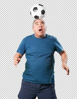 Hombre maduro jugando con balón de fútbol