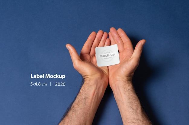 Un hombre manos sosteniendo una maqueta de etiqueta pequeña en la palma