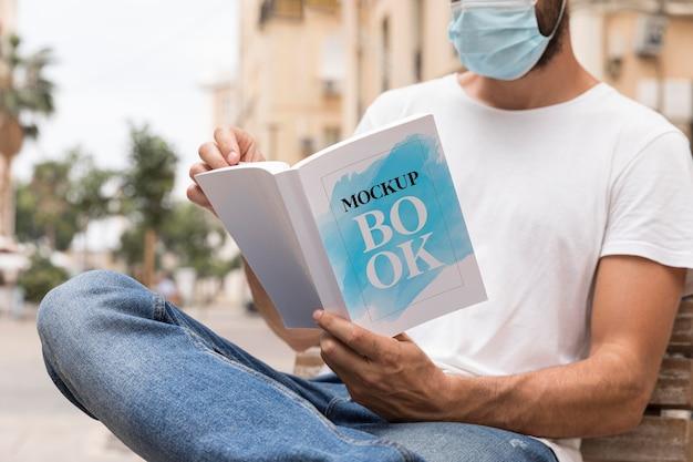 Hombre con máscara en el libro de lectura de la calle