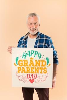 Hombre mayor presentando tabla para el día de abuelos