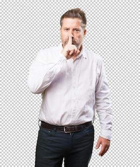 Hombre de mediana edad haciendo un gesto de silencio