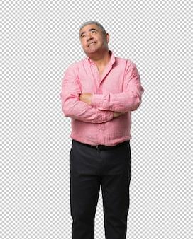 Hombre de mediana edad mirando hacia arriba, pensando en algo divertido y teniendo una idea, concepto de imaginación, feliz y emocionado