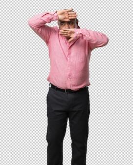 Hombre de mediana edad mirando a través de una brecha, escondiéndose y entrecerrando los ojos