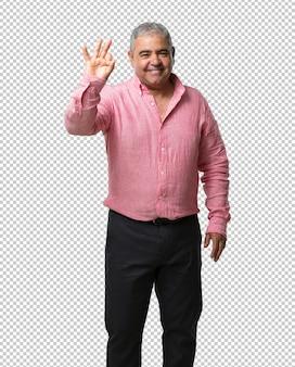 Hombre de mediana edad que muestra el número tres, símbolo de contar, concepto de matemáticas