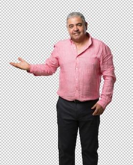 Hombre de mediana edad sosteniendo algo con las manos, mostrando un producto, sonriente y alegre, ofreciendo un objeto imaginario