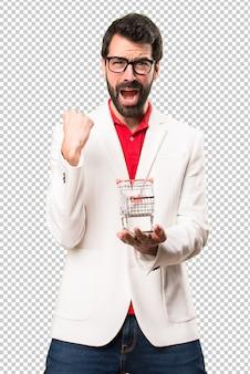 Hombre morena feliz con gafas sosteniendo un carrito de supermercado de juguete