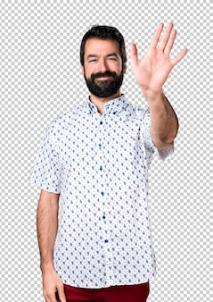 Hombre moreno guapo con barba saludando