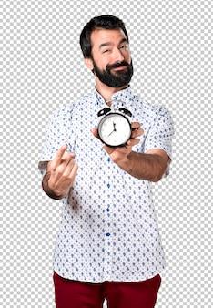 Hombre moreno hermoso con la barba que sostiene el reloj del vintage