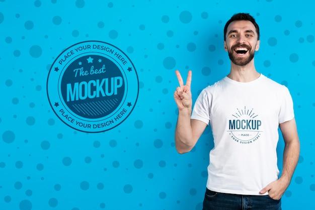 Hombre mostrando maqueta camisa signo de la paz
