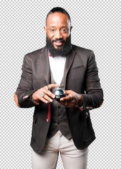 Hombre de negocios negro que sostiene una campana anillo