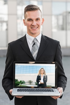 Hombre de negocios presentando maqueta de portátil