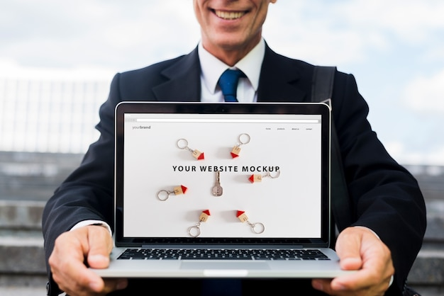 Hombre de negocios presentando mockup de portátil