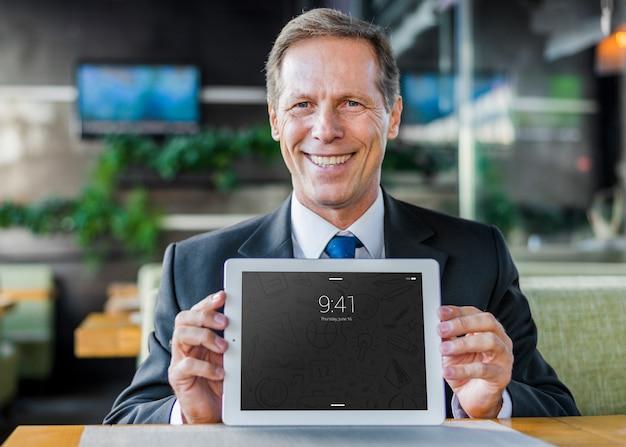 Hombre de negocios presentando mockup de tableta PSD gratuito