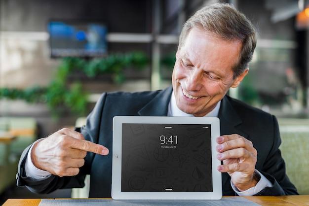 Hombre de negocios presentando mockup de tableta