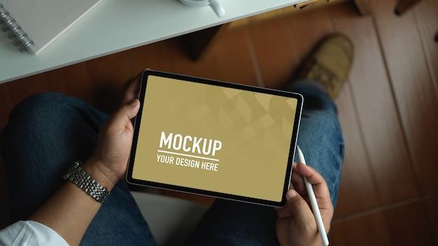 Hombre de negocios trabajando con maqueta de tableta de pantalla en blanco mientras está sentado en el espacio de trabajo