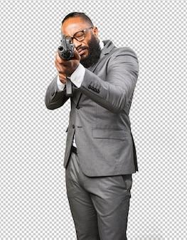 Hombre negro de negocios con una ametralladora