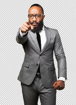 Hombre negro de negocios apuntando hacia delante