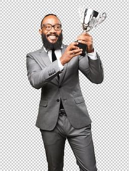 Hombre negro de negocios sosteniendo un trofeo