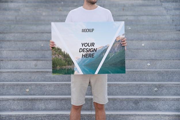 Hombre presentando mockup de cartel enfrente de escaleras