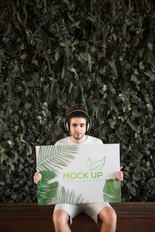 Hombre presentando mockup de cartel enfrente de hojas