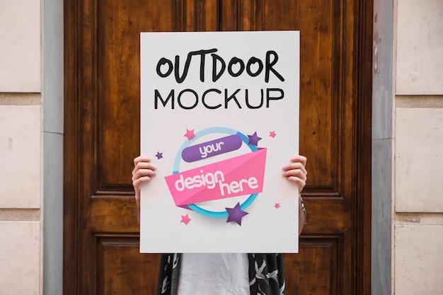 Hombre presentando mockup de cartel enfrente de puerta PSD Premium