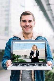 Hombre presentando mockup de portátil