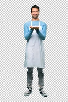 Hombre que llevaba un delantal con copyspace imaginario en la palma para insertar un anuncio