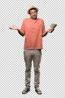 Hombre que sostiene muchos billetes haciendo un gesto sin importancia mientras levanta los hombros