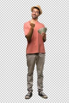 Hombre que sostiene muchos billetes invitando a venir con la mano. feliz de que hayas venido