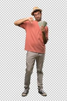 Hombre que sostiene muchos billetes que muestran el pulgar hacia abajo con ambas manos