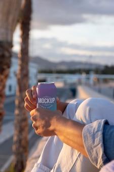 Hombre que sostiene un refresco enlatado de maqueta