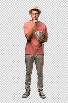 Hombre que tiene muchos billetes que muestran un gesto de silencio poniendo el dedo en la boca