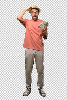 El hombre que tiene muchos billetes toma las manos en la cabeza porque tiene migraña