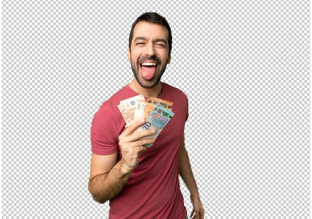 Hombre que toma mucho dinero mostrando la lengua a la cámara con aspecto divertido