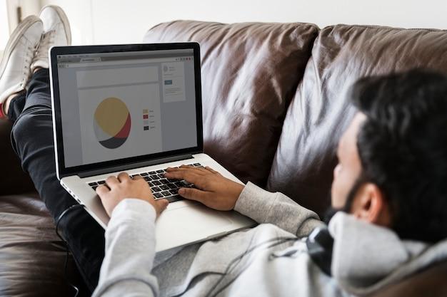 Hombre que usa la computadora portátil en el sofá