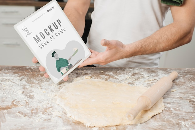 Hombre rodando masa en la cocina y sosteniendo el libro