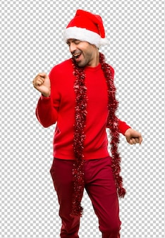 Un hombre con ropa roja que celebra las vacaciones de navidad disfruta de bailar mientras escucha m