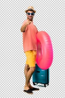 Hombre con sombrero y gafas de sol en su dedo de puntos de vacaciones de verano con una expresión de confianza