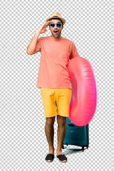 Un hombre con sombrero y gafas de sol en sus vacaciones de verano acaba de darse cuenta de algo y tiene la intención de solucionarlo.