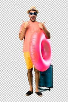 Hombre con sombrero y gafas de sol en sus vacaciones de verano dando un pulgar hacia arriba gesto con ambas manos y sonriendo. expresion alegre