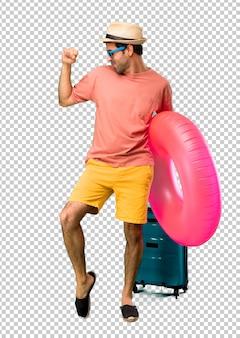 Un hombre con sombrero y gafas de sol en sus vacaciones de verano disfruta del baile mientras escucha música en una fiesta