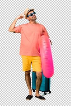 Hombre con sombrero y gafas de sol en sus vacaciones de verano con dudas y con expresión facial confundida mientras se rasca la cabeza