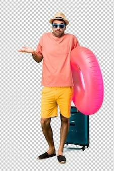 Un hombre con sombrero y gafas de sol en sus vacaciones de verano, que carece de importancia y duda hace gestos mientras levanta los hombros y las palmas de las manos.