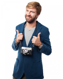 Hombre sonriendo con una cámara antigua